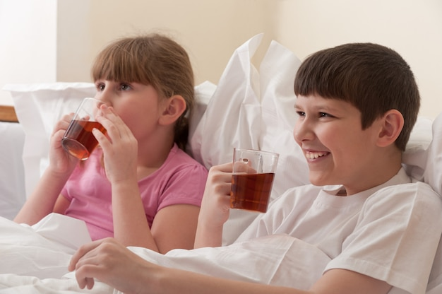 Brother and sister drinking tea while sitting in bed. indoors. close-up.