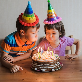 Brother and sister eating a birthday cake with candles blowing out and hugging.