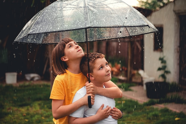 Brother and sister enjoying rain