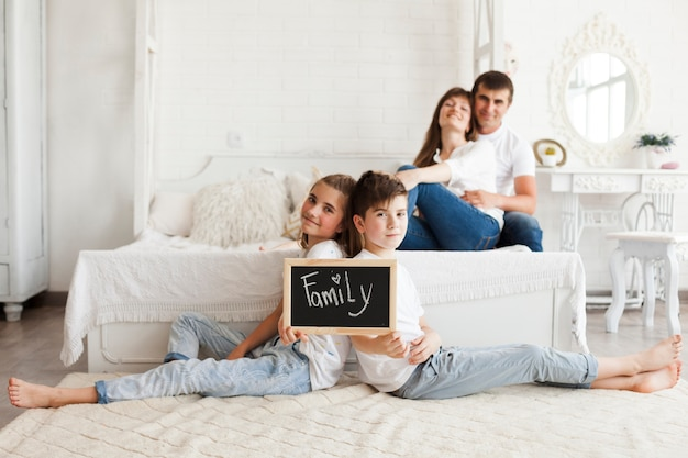 Brother and sister holding slate with family text sitting on carpet in front of their parent