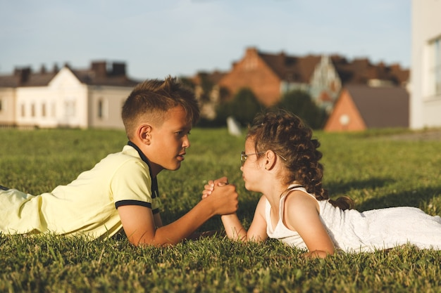 Brother and sister lying on the grass are engaged in arm wrestling.