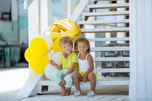 Brother and sister outdoors sitting on white steps and holding white balloons.