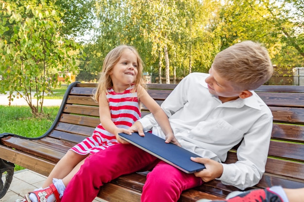 Brother and sister in the park on a bench take away a laptop from each other