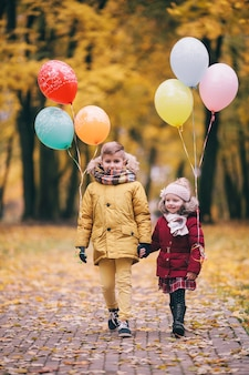 Brother and sister playing with balloons in an autumn park