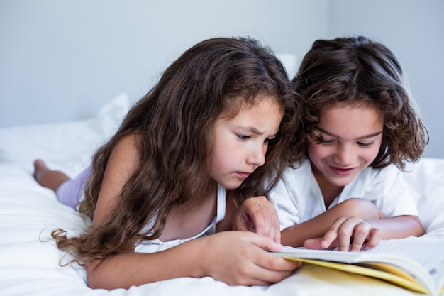 Brother and sister reading book together on bed
