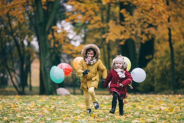 Brother and sister running through an autumn park with balloons