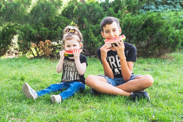 Brother and sister sitting in garden eating watermelon