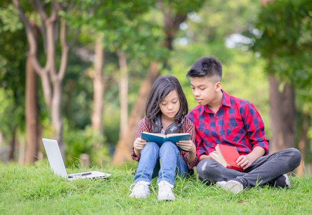 Brother and sister sitting on the grass and reading a book