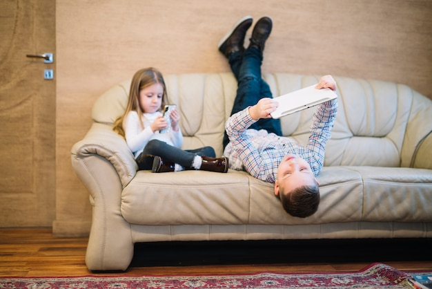 Brother and sister sitting on sofa using mobile phone and digital tablet