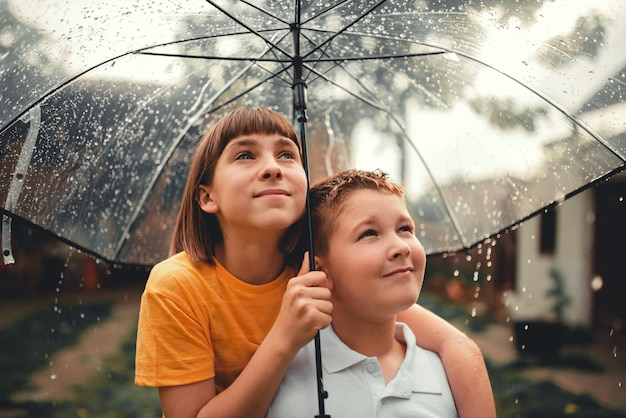 Brother and sister standing underneath umbrella
