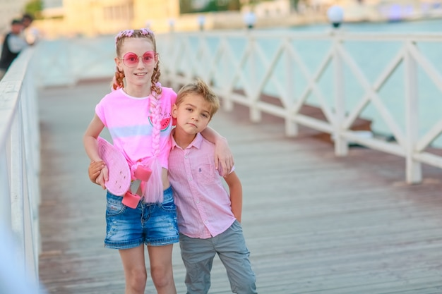Brother and sister together walk and have fun on the street without people