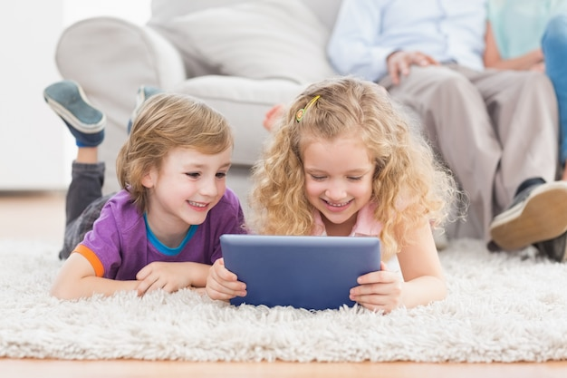 Brother and sister using digital tablet on rug