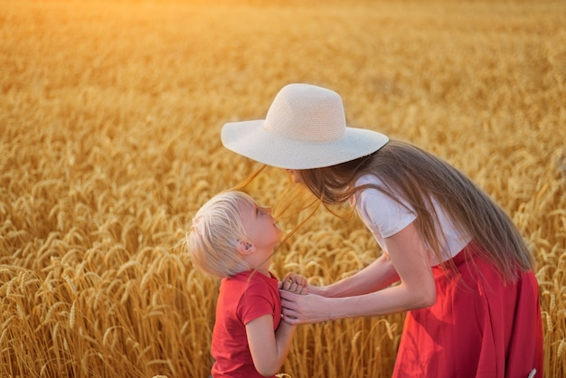 Brother and sister walking through wheat field. siblings play on field