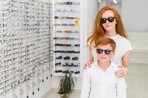 Brother and sister with black eyeglasses standing together in optics shop