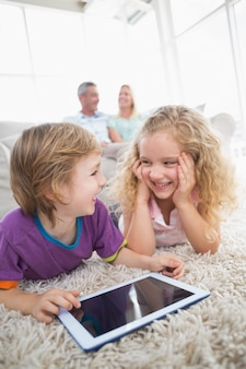 Brother and sister with digital tablet on rug