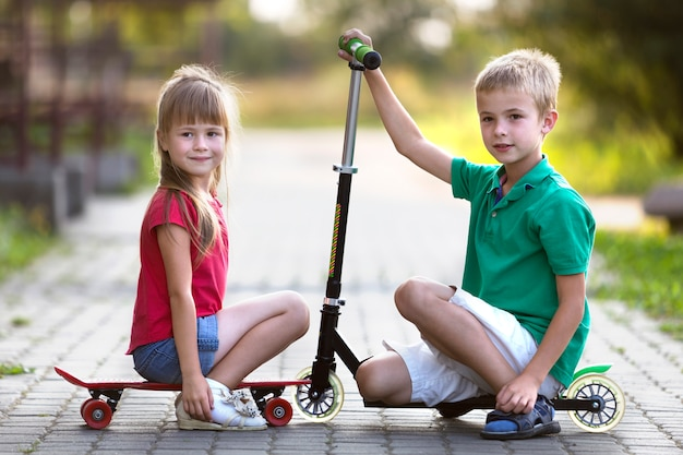 Brother and sister with scooter and skateboard