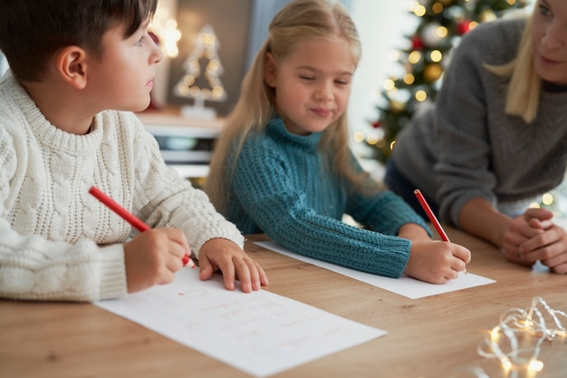 Brother and sister writing a letter to santa claus