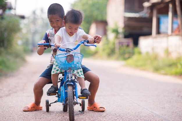 Brother teaches his boy to ride a bike in park