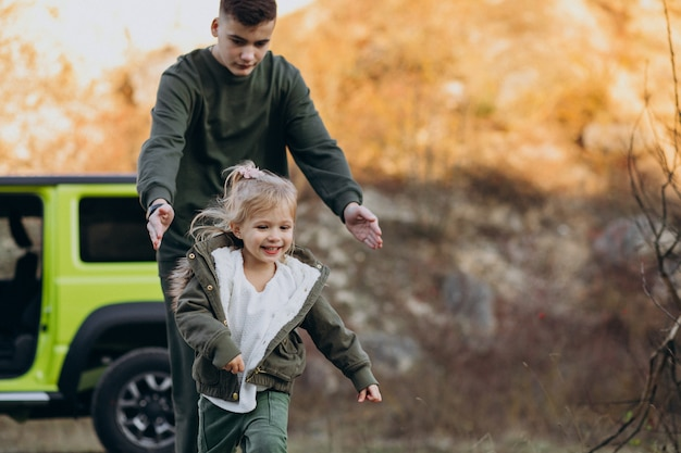 Brother with little sister having fun by car