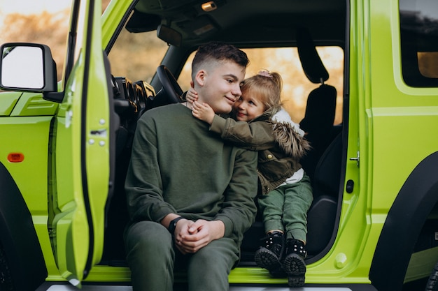 Brother with little sister sitting in green car