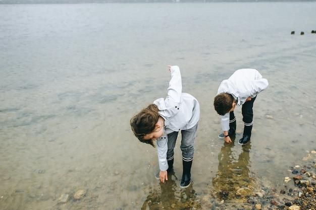 姉と弟はレインコートを着て海で楽しんで