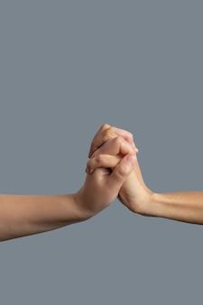 Братство. крупный план: светлокожие и темнокожие руки, сцепленные вместе.