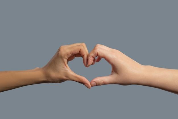 Братство человечества. крупный план светлокожих и темнокожих рук, формирующих форму сердца