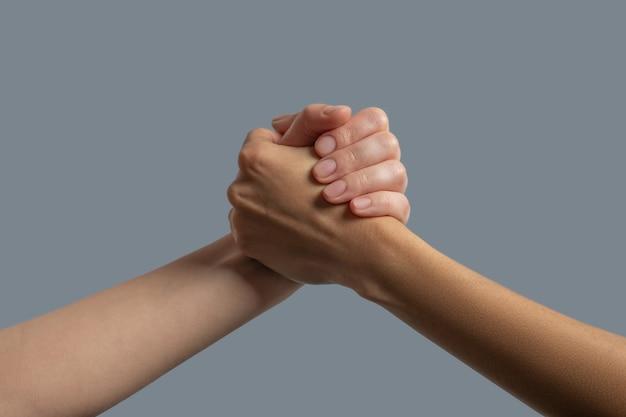 Братство человечества. крупный план светлокожих и темнокожих людей, обнимающих руки