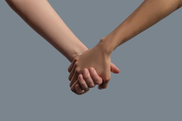 Братство человечества. крупный план светлокожих и темнокожих людей, держащихся за руки