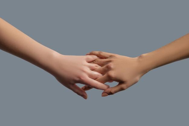 Братство человечества. крупный план людей разных рас, сцепивших пальцы