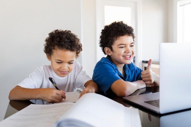 새로운 정상 기간 동안 집에서 숙제하는 형제