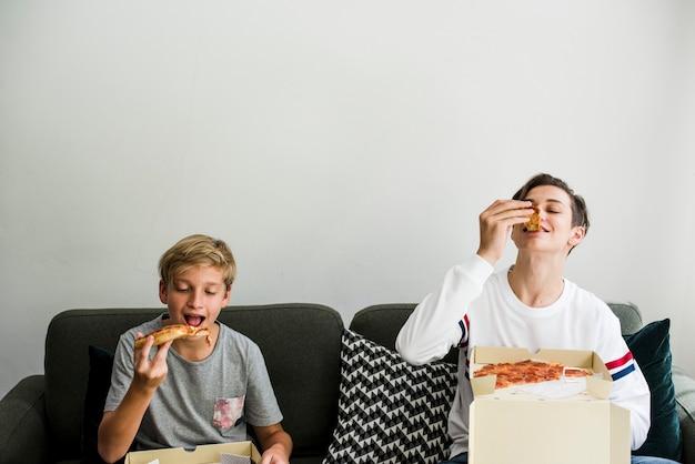 ソファでピザを食べる兄弟