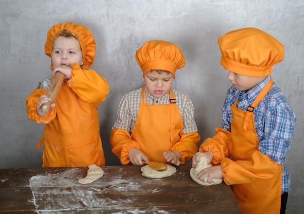 兄弟はお母さんがソーセージとチーズでピザを作るのを手伝います