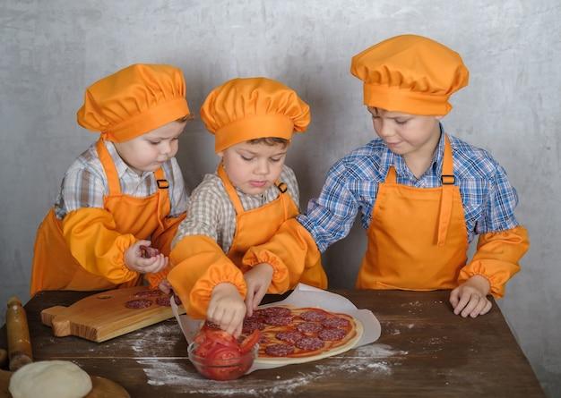 형제는 엄마가 소시지와 치즈로 피자를 요리하도록 도와줍니다.
