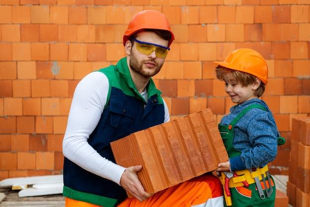 Братья помогают концептуальному каменщику, устанавливая кирпичи на стройке, строителю работают с кирпичом ...