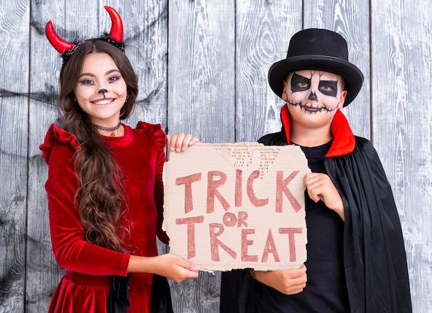 Brothers holding trick or treat sign in halloween costumes