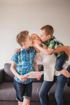 母の日に母親にキスをする兄弟