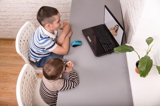 E- 학습 동안 노트북을보고 형제. 디지털 테이블을 사용하는 소년