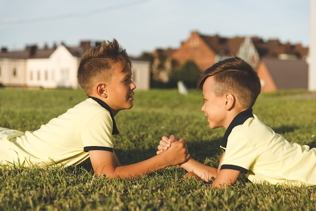 Brothers lying on the grass are engaged in arm wrestling.