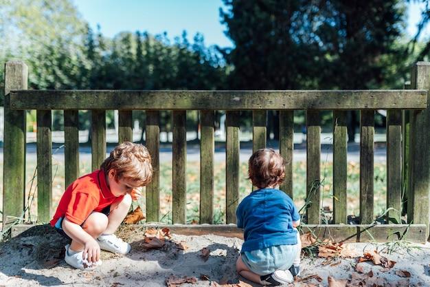 모래와 마른 나무 잎으로 놀이터의 나무 울타리에서 노는 형제들