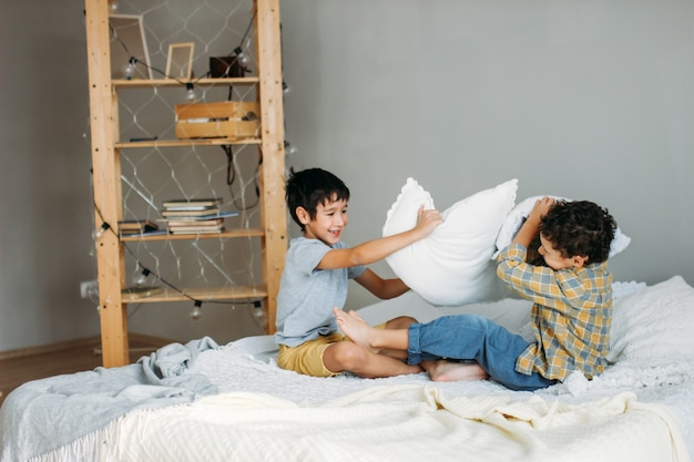 Brothers playing with pillows on parents bed at home