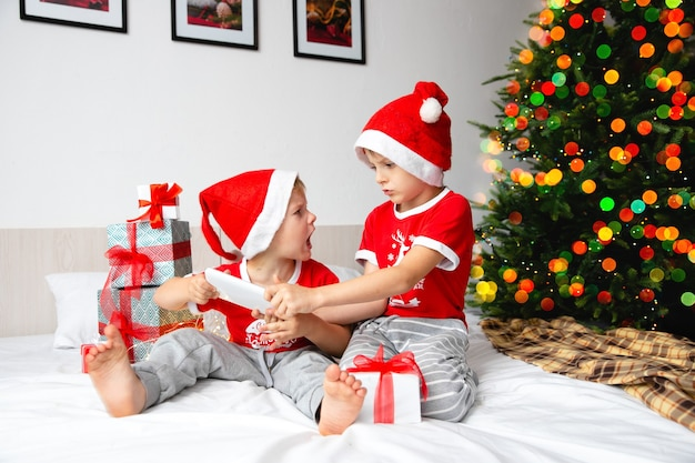 Brothers in santa red hats fighting over a gift
