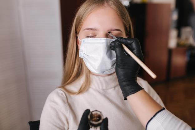 黒の保護マスクの眉マスターは、美しいブロンドの髪の女性のために眉にヘナを適用します