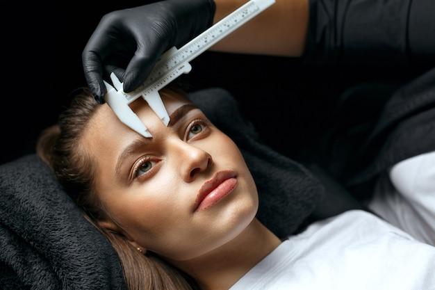 Brow master измеряет брови линейкой перед процедурой татуировки в салоне красоты