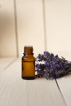 Browbrown glass bottle with fragrant lavender oil and a bouquet of flowers.