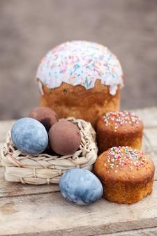 Коричневые и синие яйца с куличом на деревянных фоне. пасхальные праздники