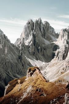 昼間の白い曇り空の下の茶色と灰色の岩山
