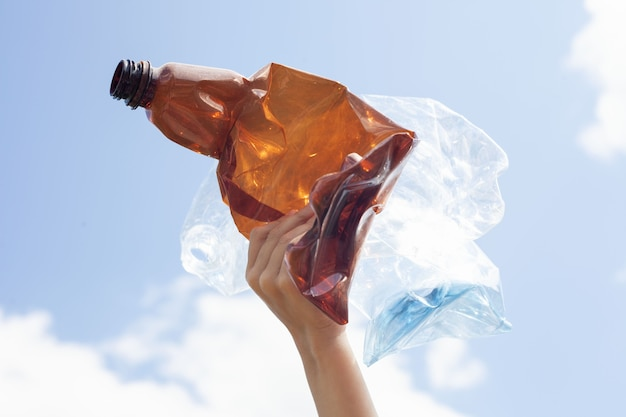 茶色と軽いペットボトルは押しつぶされ、ブロックのある青い空を背景に子供の手にあります。