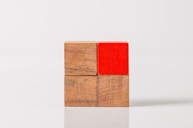 흰 벽에 고립 된 갈색과 빨간색 나무 기하학적 도형 큐브