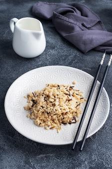 Коричневый и неочищенный рис на тарелке с палочками для еды.